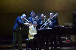 sekcja puzonów przy dyrygencie orkiestry siedzącym przy fortepianie