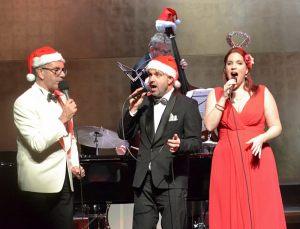 na pierwszym planie troje wokalistów w czapkach św. Mikołaja