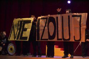 artyści stoją na scenie i prezentują planszę z napisem: nie izoluj