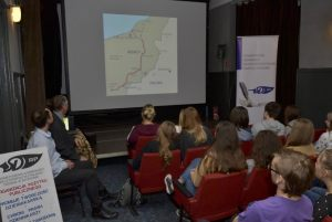 młodzież ogląda mapy wojskowe i słucha prelekcji