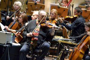Michał Urbaniak siedzi, trzyma w ręku skrzypce koncentrując się przed następnym utworem
