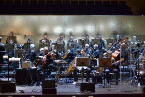 Michał Urbaniak grający na skrzypcach na tle orkiestry Filharmonii Szczecińskiej