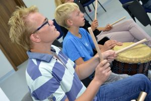 uczniowie uczą się grać na bębnach afrykańskich