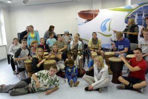 cała grupa wraz z instruktorką po zajęciach z tańca afrykańskiego z towarzyszeniem bębnów afrykańskich